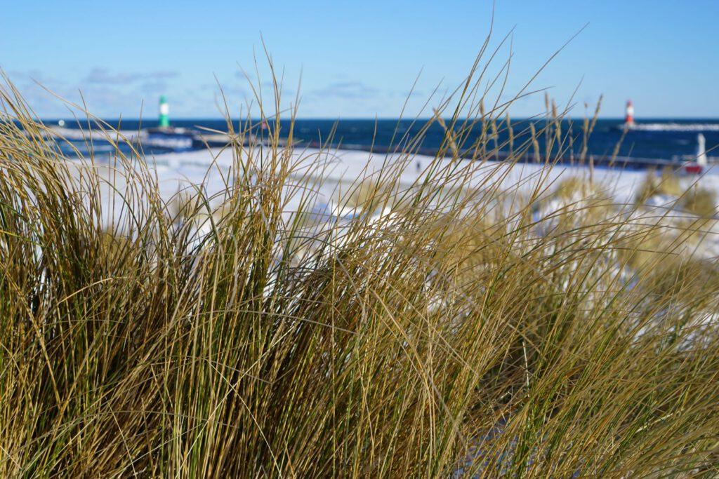 Strahlende Wintereindrücke aus Warnemünde Strand im Winter mit Leuchtturm